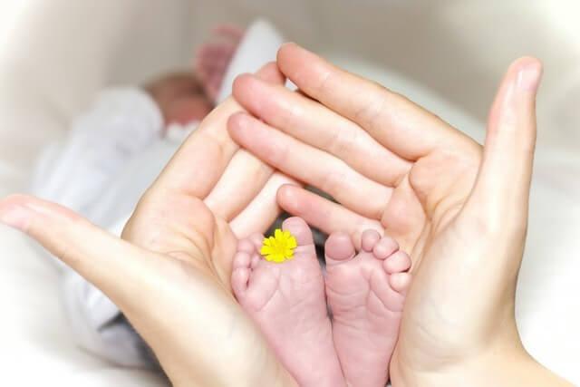 Pieds de bébé dans les mains de maman