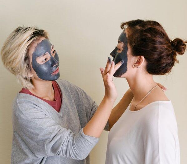 Application d'argile noire sur le visage
