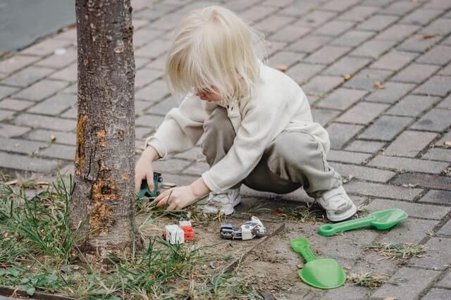 Petite fille blonde qui joue avec une pelle en plastique