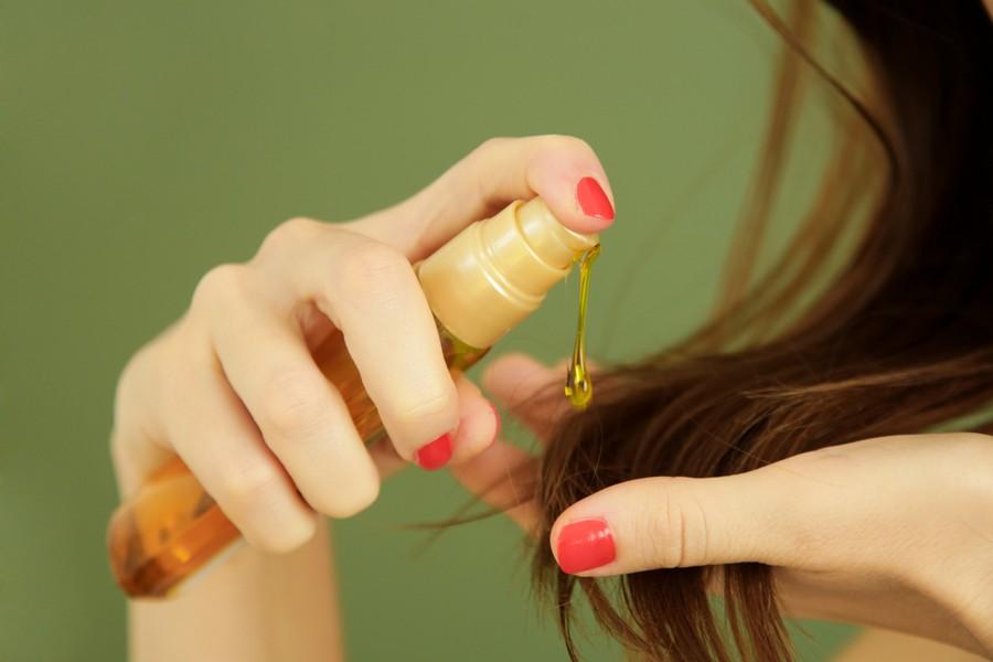 Femme qui se met de l'huile sur les cheveux