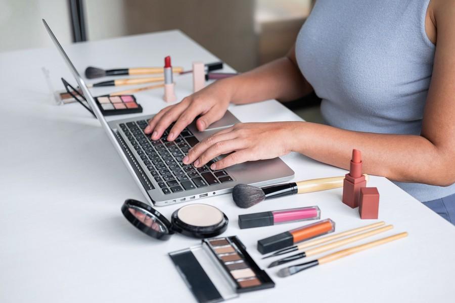Femme qui est sur son ordinateur avec du maquillage à côté
