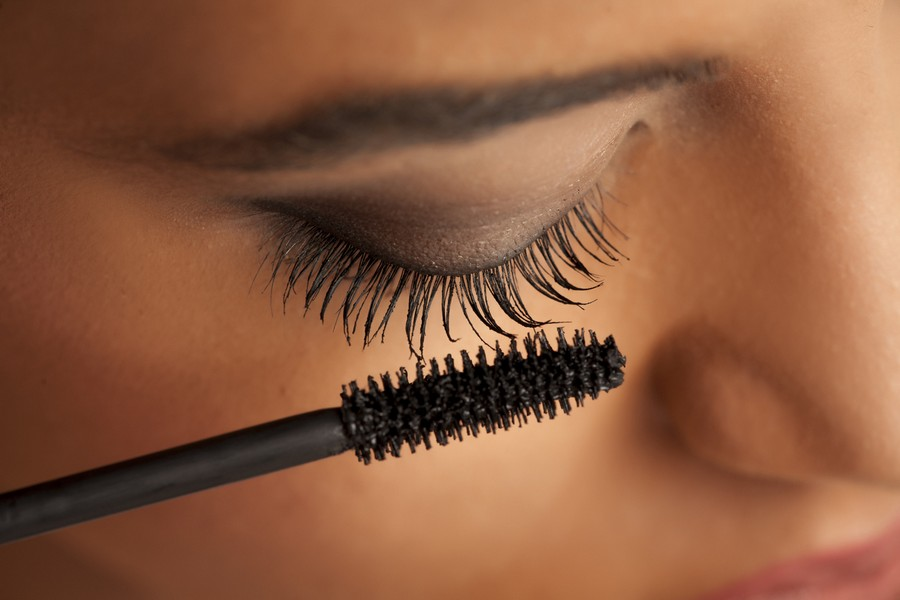 femme avec une brosse de mascara près des cils