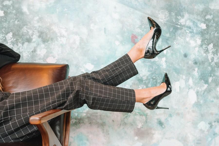 jambes d'une femme en talons assise sur un fauteuil