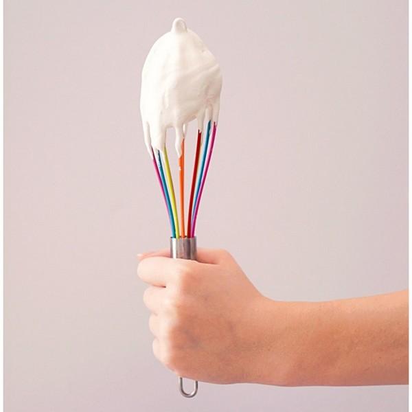 main qui tient un fouet avec de la crème chantilly dessus