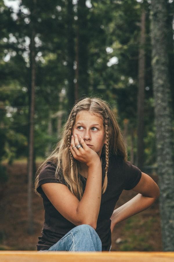 adolescente dans la forêt coiffée avec deux nattes sur le devant des cheveux