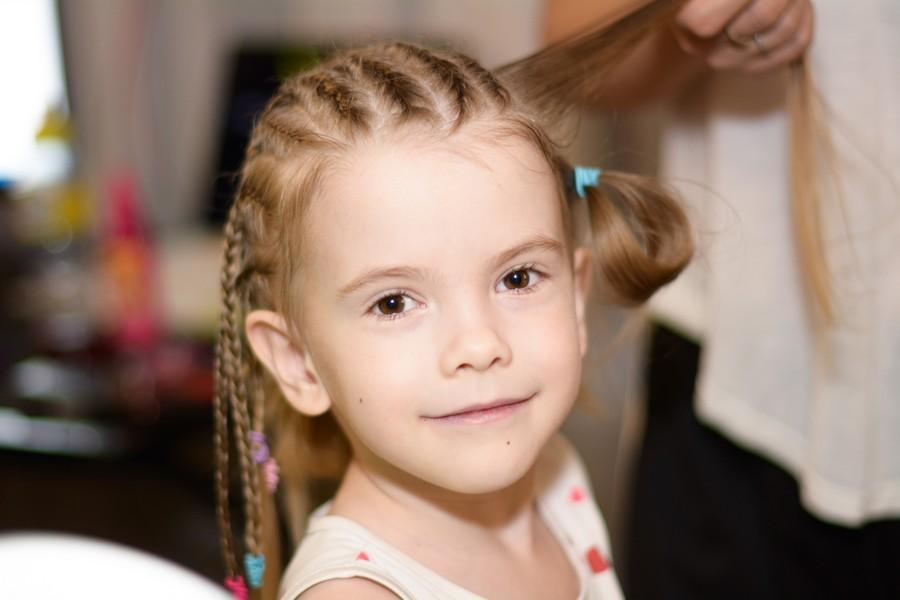 petite fille en train de se faire coiffer avec des élastiques