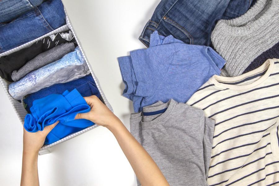 mains d'une personne qui range des vêtements d'enfant